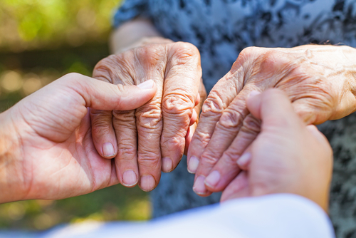 man holding hands of parkinson patient